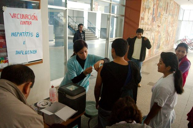 Enfermera vacunando a estudiante contra la hepatis B y la gripe.